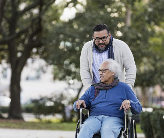Adult man walking outside with his elderly father who is in a wheelchair